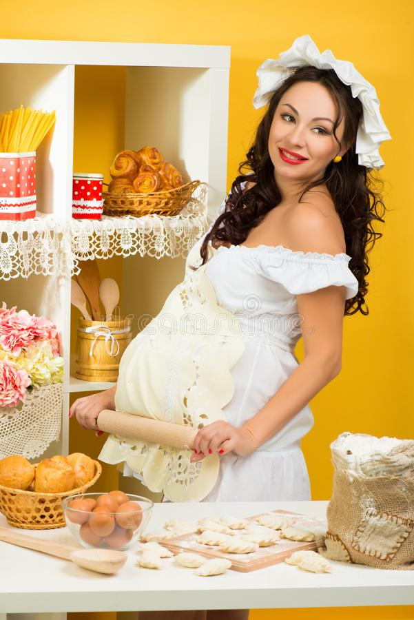 A professional pregnant chef in the kitchen prepares the dough with flour to make the baking royalty free stock photography