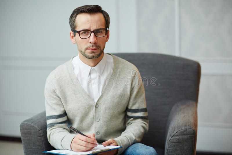 Professional psychiatrist. Serious psychiatrist in armchair making notes on paper stock photography