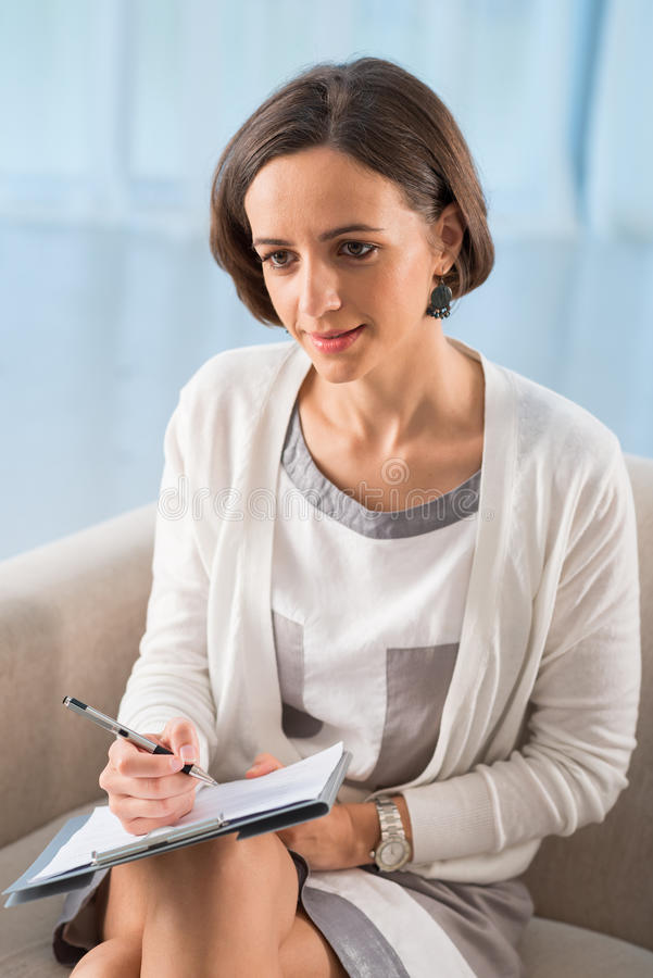 Professional psychiatrist. Vertical image of a young professional psychiatrist at therapy session stock image
