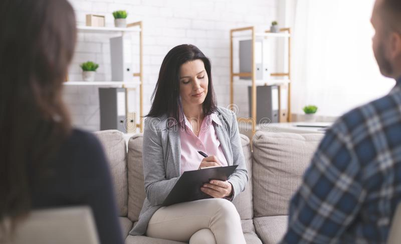 Professional psychologist taking notes at couple meeting with patients stock photo
