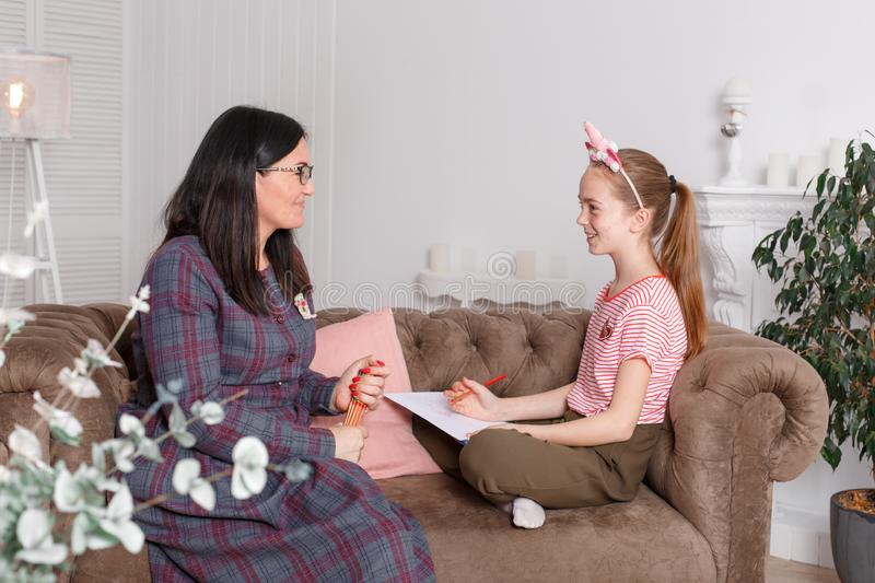 Professional psychologist with a teenage girl. Woman proposes to draw a picture. The method of work of a child psychotherapist stock photo
