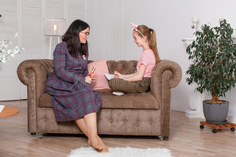 Professional psychologist with a teenage girl. Woman proposes to draw a picture. The method of work of a child psychotherapist.  royalty free stock photo