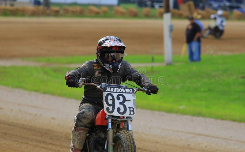 Professional racer on the track. Dirt bike kicks up the dust as he races the motorcycle track event at the professional motorcycle racing event on the dirt oval stock photography