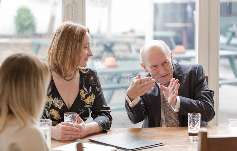 Professional real people, young adult woman, senior man, having. Informal business meeting in pub at glass of dark beer. Candid unposed horizontal shot royalty free stock photos