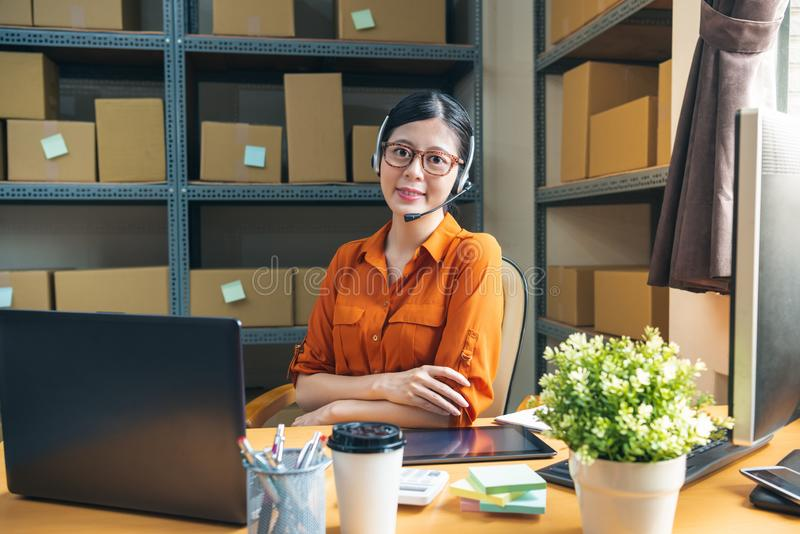 Professional receptionist sitting in warehouse. Professional receptionist sitting on her office desk in warehouse, wearing earphone face to camera smiling stock photo