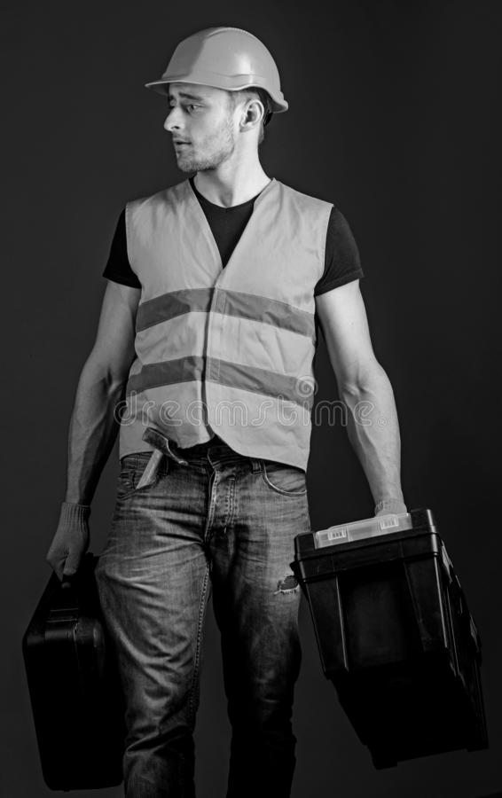 Professional repairman concept. Worker, handyman, repairman, builder on calm face carries bags with professional tools royalty free stock images