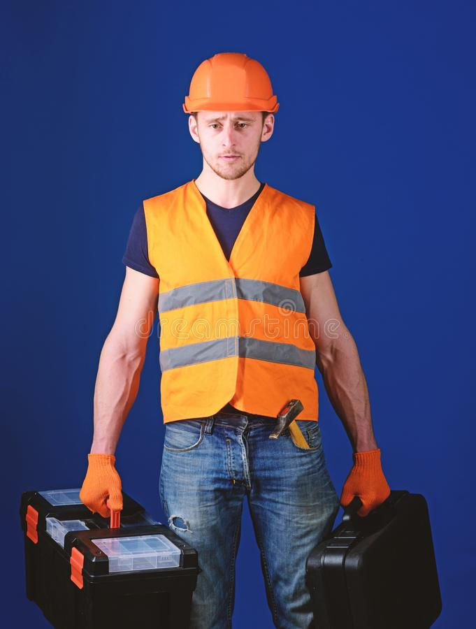 Professional repairman concept. Worker, handyman, repairman, builder on strict face carries bags with professional tools royalty free stock photo