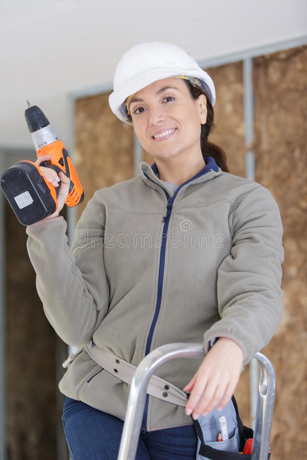 Professional repairwoman posing and holding drill royalty free stock photography