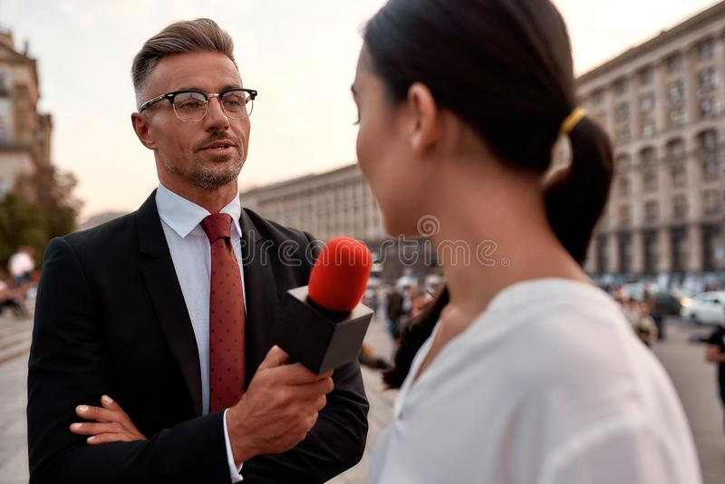 Professional reporter interviewing woman on urban street. Journalism industry, live streaming concept stock photos