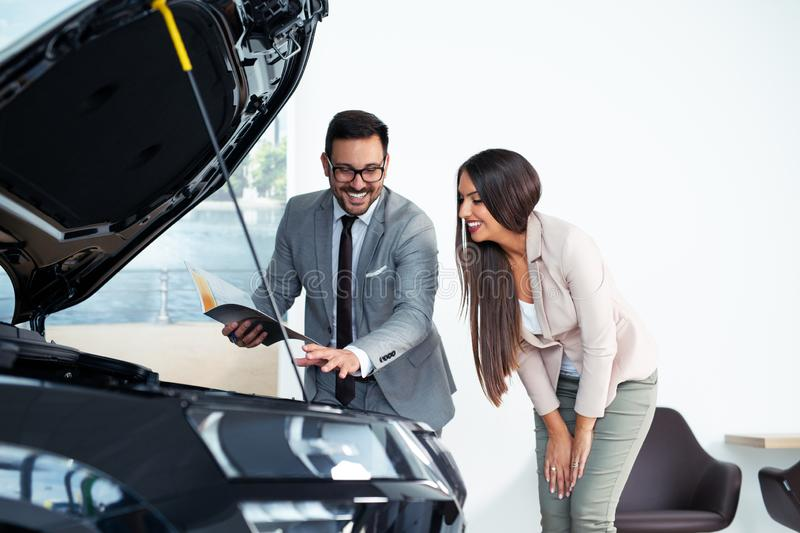 Professional salesperson selling cars at dealership to buyer royalty free stock photography