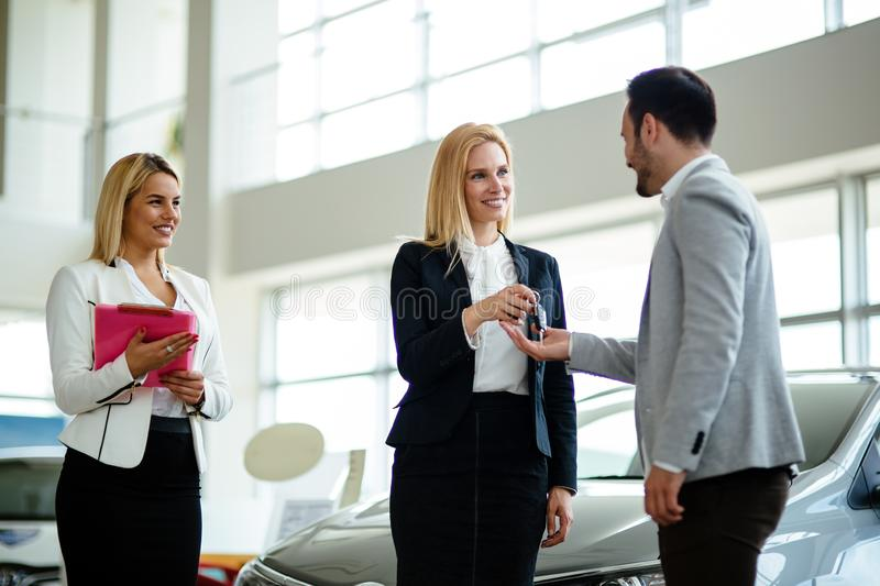 Professional salesperson during work with customer at car dealership. Giving keys to new car owner. Salesperson during work with customer at car dealership stock photography