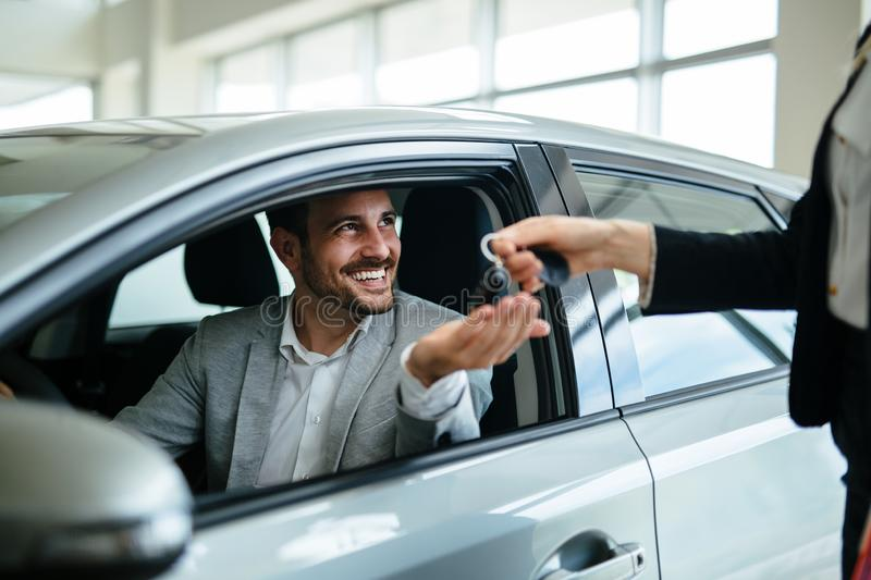 Professional salesperson during work with customer at car dealership. Giving keys to new car owner. Salesperson during work with customer at car dealership stock images