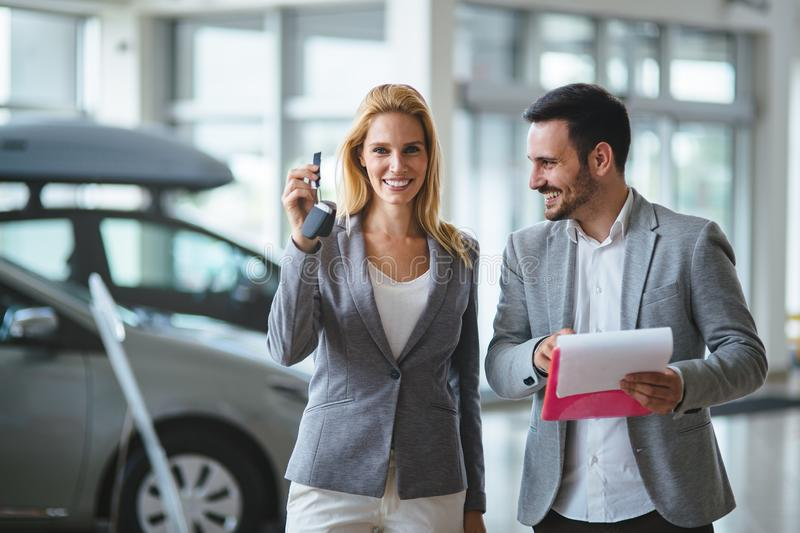 Professional salesperson during work with customer at car dealership. Giving keys to new car owner. Salesperson during work with customer at car dealership royalty free stock images