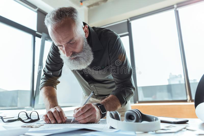 Professional serious worker is laboring on his design plan royalty free stock images