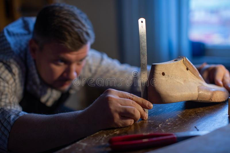 A professional shoemaker measures a wooden Shoe block with a ruler. stock photography