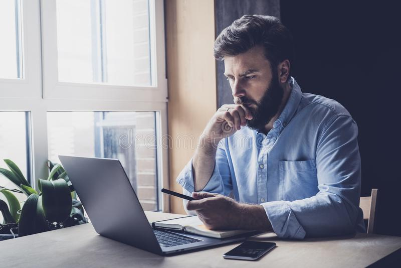 Professional sitting in office in front of laptop. Home-based student getting distant education. Serious man working on desktop. Professional sitting in office stock image