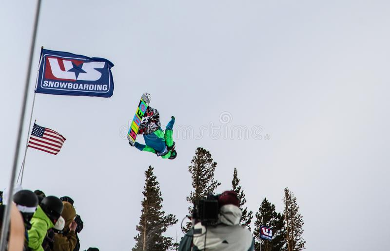 Snowboarder catches air at the half-pipe competition, Mammoth Mountain, California USA. Professional skiers and snowboarders get some air and practice grabs in stock photo