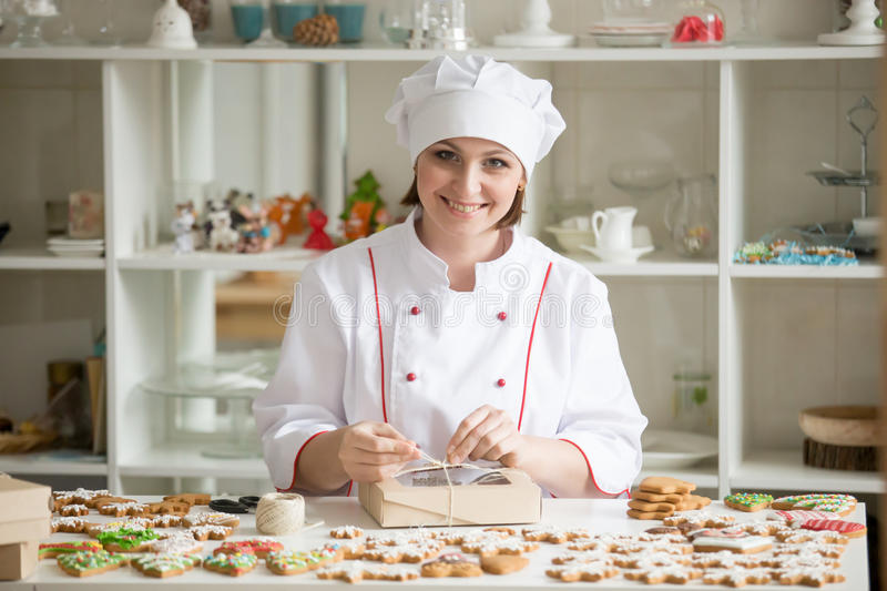 Professional smiling confectioner wrapping a box with cookies stock photos