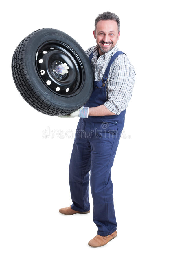 Professional smiling mechanic working with car tire royalty free stock photos