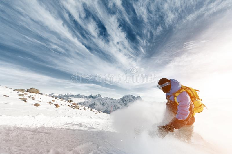 Professional snowboarder with a backpack leaving the cloud of snowy powder at sunset on a background of epic clouds and stock photos