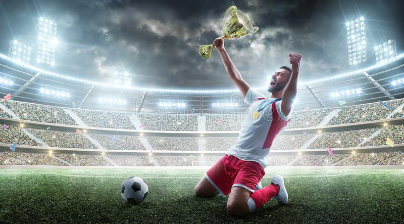 Professional soccer player celebrates winning the open stadium. Soccer player holds a trophy. Medal on the neck. The stock photos