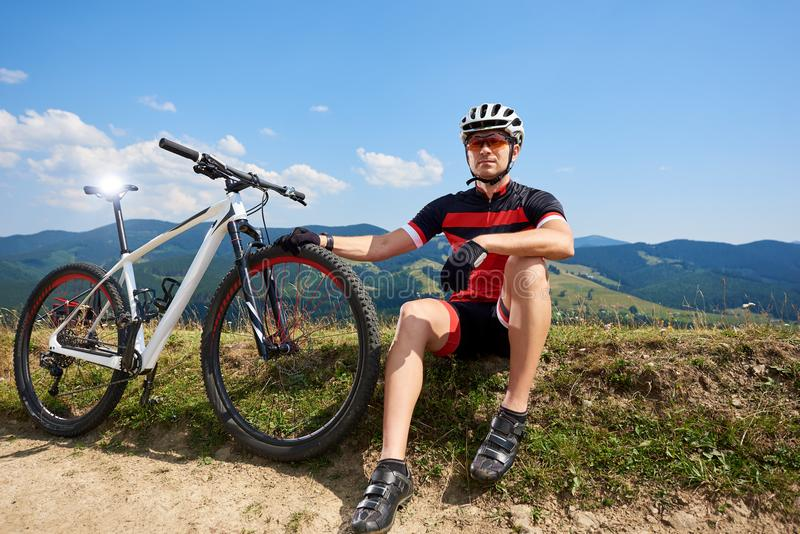 Professional sportsman cyclist in sportswear, helmet sitting near his bicycle on grassy roadside. Resting after cycling bike in mountains on sunny summer day royalty free stock photography