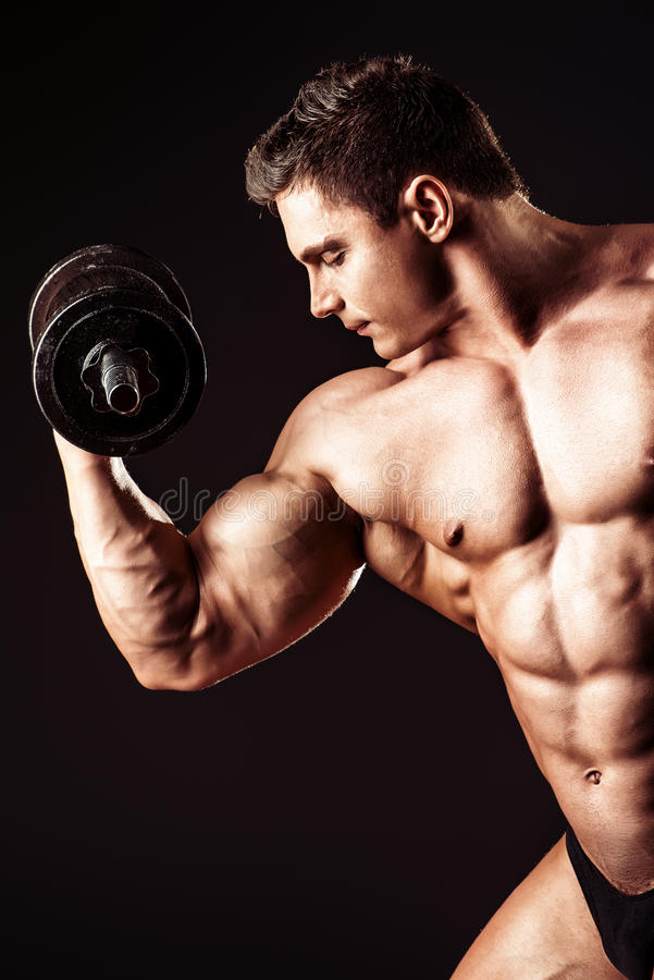 Professional sportsman. Portrait of a handsome muscular bodybuilder posing with dumbbells over black background royalty free stock images