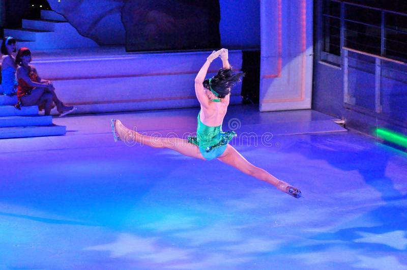 Split jump. Professional sportsmans ice skaters performing in an ice show production onboard cruise ship Adventure of the Seas royalty free stock image