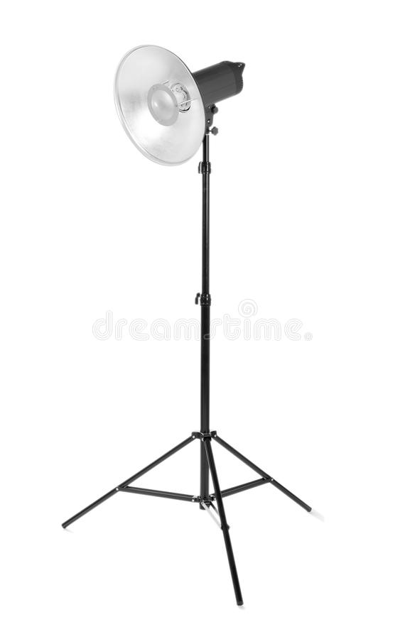 Professional studio flash light isolated on a white background. Studio lighting on a tripod. Photographic equipment. Professional photo studio flashlight stock photo