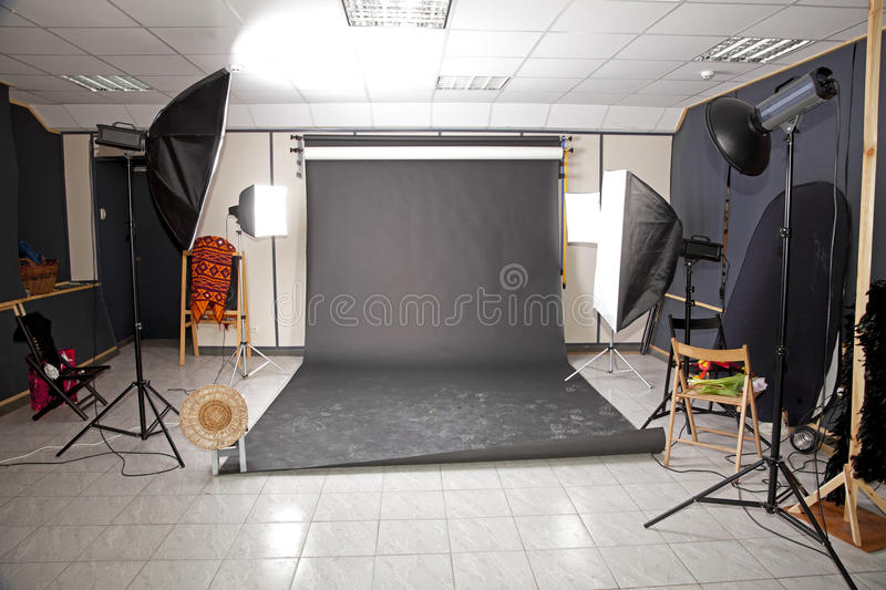 Professional studio interior with black background. And number of flashlights royalty free stock photography