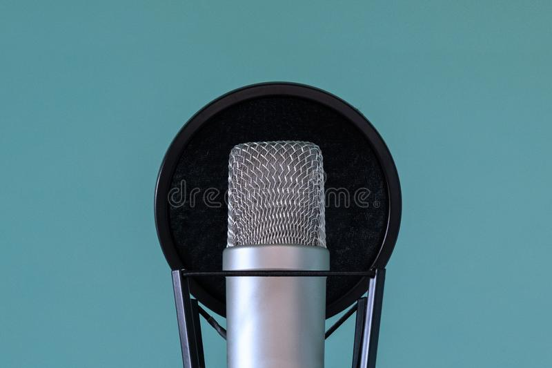 Professional studio microphone with pop filter and shock absorber on a blue background. The concept of high-quality sound and stock image