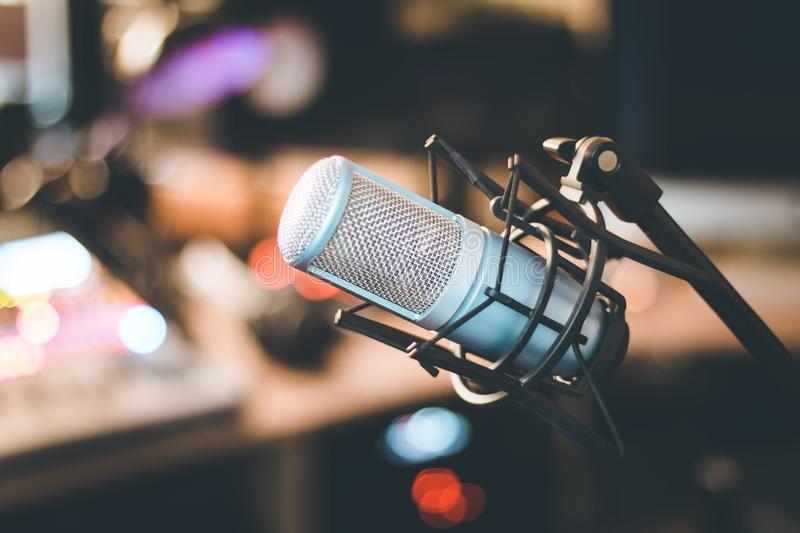 Professional studio microphone, recording studio, equipment in the blurry background. Microphone in a professional recording or radio studio, equipment in the stock image