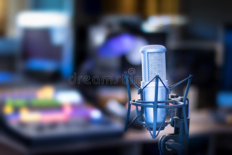 Professional studio microphone, recording studio, equipment in the blurry background. Microphone in a professional recording or radio studio, equipment in the stock photos