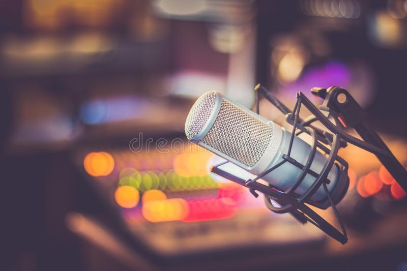 Professional studio microphone, recording studio, equipment in the blurry background. Microphone in a professional recording or radio studio, equipment in the stock images