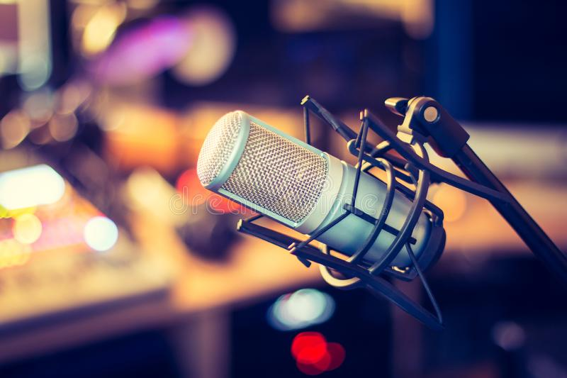 Professional studio microphone, recording studio, equipment in the blurry background. Microphone in a professional recording or radio studio, equipment in the royalty free stock photography