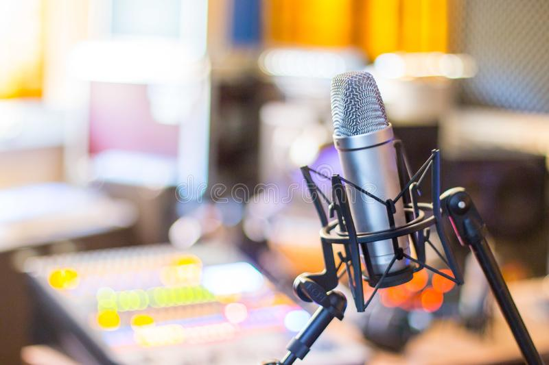 Professional studio microphone, recording studio, equipment in the blurry background. Microphone in a professional recording or radio studio, equipment in the stock photography