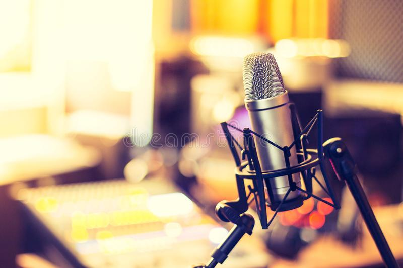 Professional studio microphone, recording studio, equipment in the blurry background. Microphone in a professional recording or radio studio, equipment in the royalty free stock images