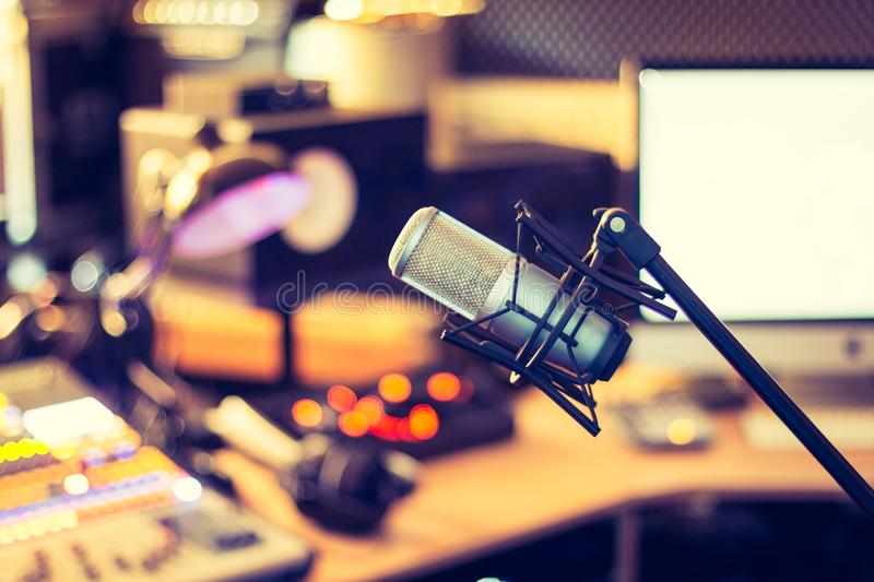 Professional studio microphone, recording studio, equipment in the blurry background. Microphone in a professional recording or radio studio, equipment in the stock photo