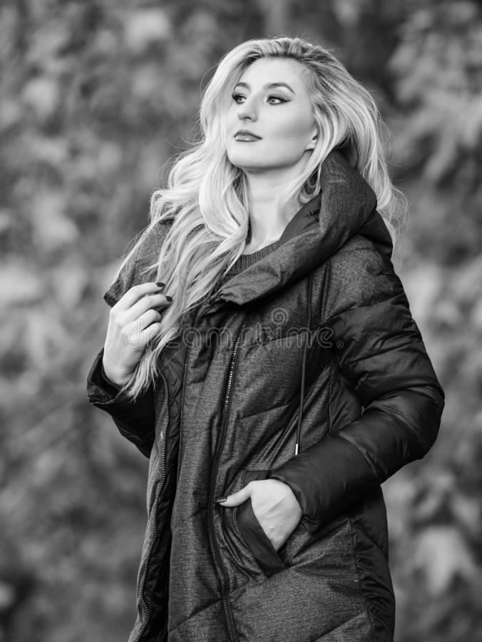 Professional stylist advice. Woman wear extra volume jacket. Girl fashionable blonde walk autumn park. Jackets everyone. Should have. Best puffer coat to buy royalty free stock photo