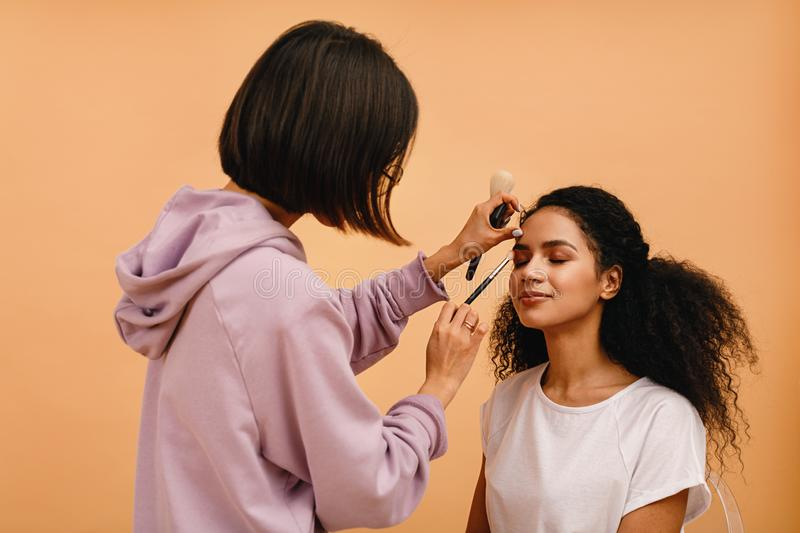 Professional stylist corrects makeup. During photo shoot royalty free stock photo