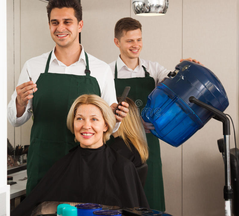 Professional stylist cutting hair of elderly blonde in hairdresser salon royalty free stock images