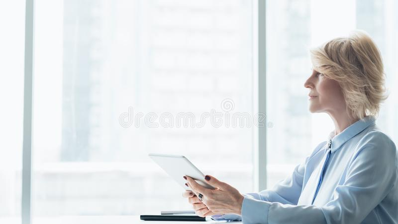 Professional success mature female business leader. Professional success. Mature female business leader. Side view of blonde woman sitting with tablet against royalty free stock images