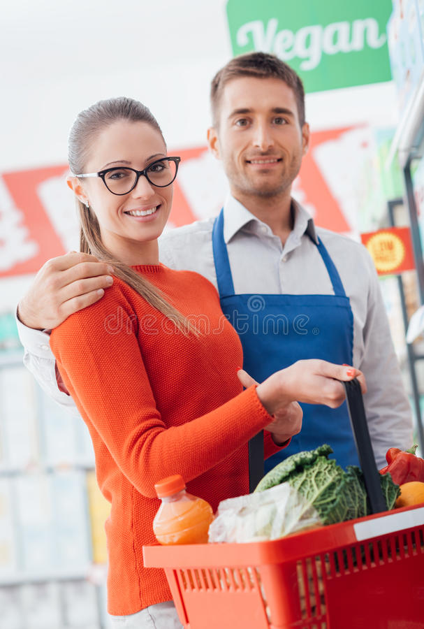 Professional supermarket clerk and happy customer royalty free stock photos
