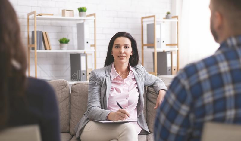 Confident psychologist working at marital therapy session. Professional support. Confident psychologist at marital therapy session, looking at camera royalty free stock photography