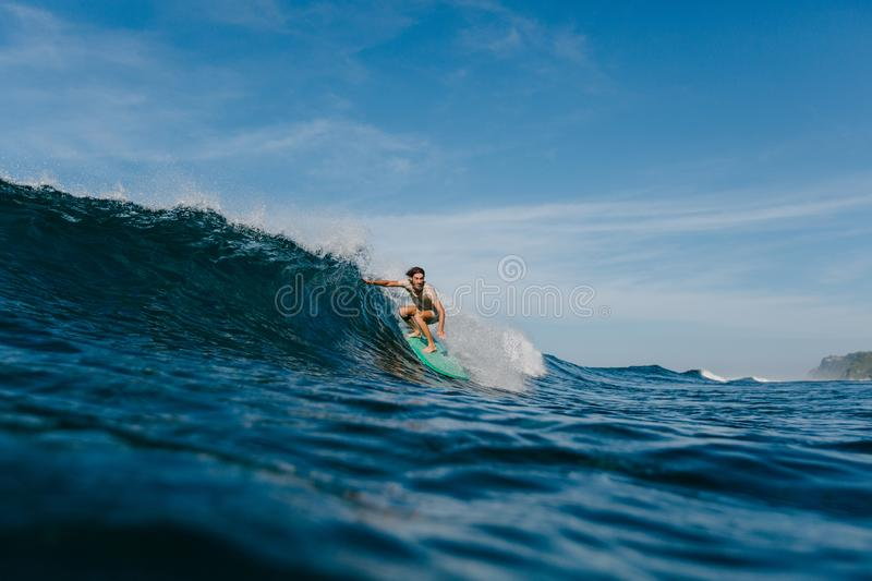 professional surfer in wet t-shirt riding waves on surfboard stock images