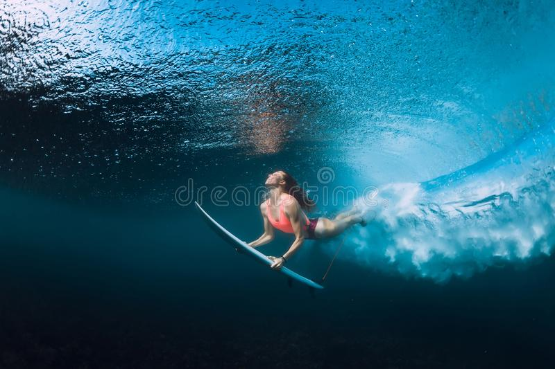 Professional surfer woman with surfboard dive underwater with under big ocean wave. stock image