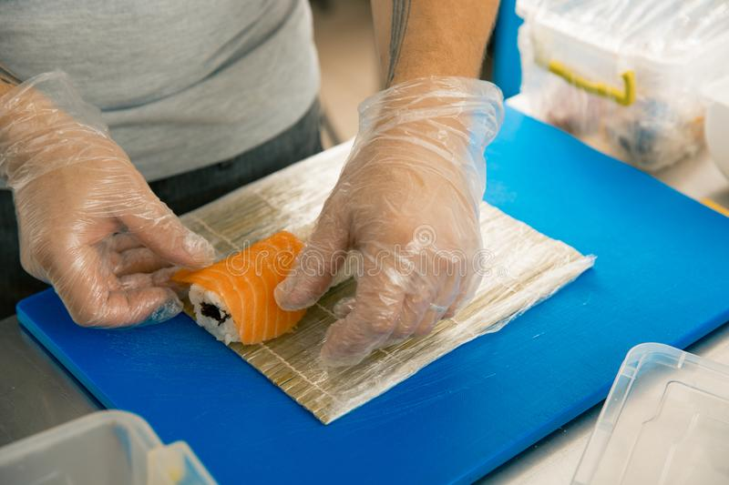 Professional sushi chef preparing roll at commercial kitchen. Cook puts the salmon on roll. Japanese cuisine recipes stock photos
