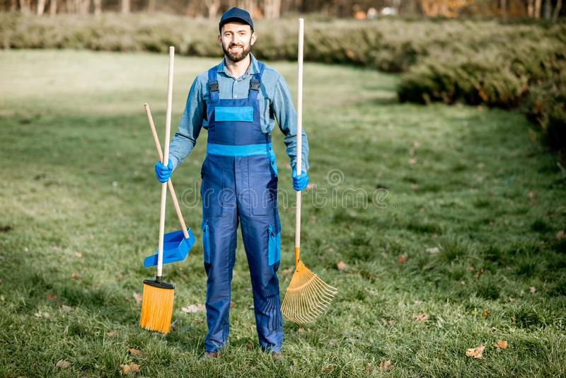 Professional sweeper with cleaning tools outdoors royalty free stock photography