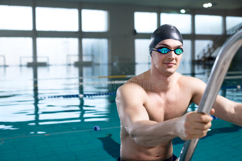 Professional swimmer on the ladder. Professional swimmer after the race, using ladder, exiting the pool. Looking into the camera, copy space on the left side of royalty free stock images