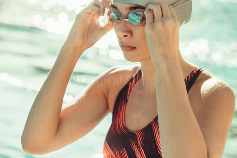 Professional swimmer ready for swimming training. Close up of professional female swimmer in swimsuit adjusting her goggles. Woman swimmer ready for swimming royalty free stock image